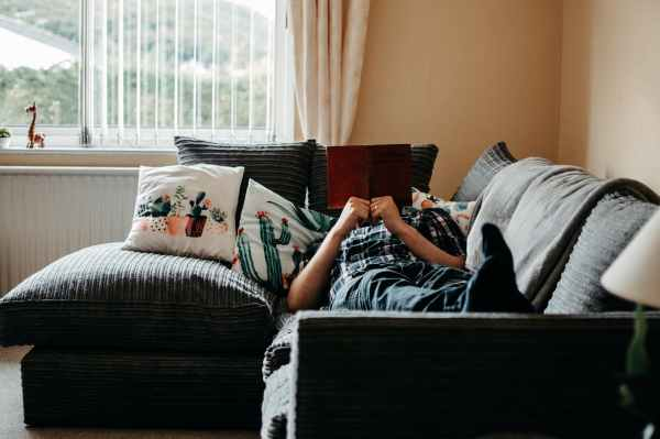 person lying on couch reading a book